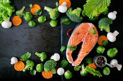 Raw salmon steak and ingredients for cooking. Raw salmon steak and ingredients for cooking on a dark background in a rustic style. Top view Stock Photography