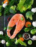 Raw salmon steak and ingredients for cooking. Raw salmon steak and ingredients for cooking on a dark background in a rustic style. Top view Stock Photo