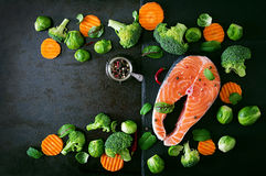Raw salmon steak and ingredients for cooking. Raw salmon steak and ingredients for cooking on a dark background in a rustic style. Top view Royalty Free Stock Photos