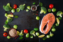 Raw salmon steak and ingredients for cooking. Raw salmon steak and ingredients for cooking on a dark background in a rustic style. Top view Royalty Free Stock Photography