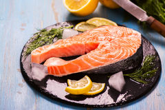 Raw salmon steak with lemon and herbs Stock Photography