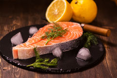 Raw salmon steak with lemon and herbs Royalty Free Stock Photography