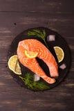Raw salmon steak with lemon and herbs Stock Photo