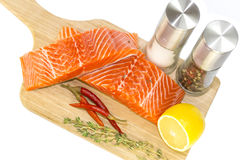 Raw salmon steak. With lemon and spices on a cutting board Stock Photography