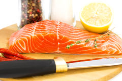 Raw salmon steak. With lemon and spices on a cutting board Stock Images