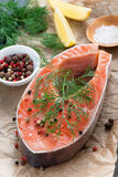 Raw salmon steak, lemon, spices prepared for cooking, vertical Royalty Free Stock Photos