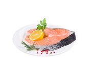 Raw salmon steak with parsley and lemon slice. Isolated on a white background Royalty Free Stock Photo