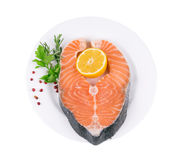 Raw salmon steak with parsley and lemon slice. On a white background Royalty Free Stock Photo