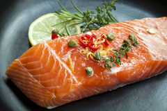 Raw Salmon Steak. Ready for cooking.  Garnished with capers, lemon, chili and herbs Royalty Free Stock Photo