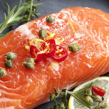 Raw Salmon Steak. Ready for cooking.  Garnished with capers, lemon, chili and herbs Stock Photos