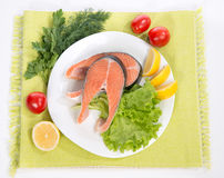 Raw salmon steak red fish on a plate decorated with vegetables Stock Photos