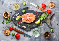Raw salmon steak. On retro cutting board.Fish salmon steak on a fish shaped board stock photo