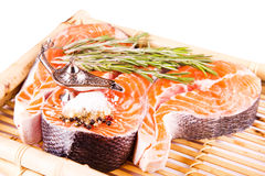 Raw salmon steak with rosemary on a bamboo board Stock Photo