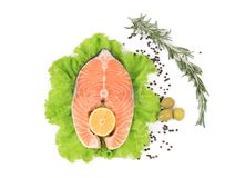 Raw salmon steak with rosemary and lemon. Isolated on a white background Royalty Free Stock Image