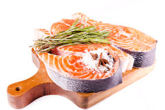 Raw salmon steak with rosemary on a wooden board. Isolated on white Royalty Free Stock Photos