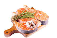 Raw salmon steak with rosemary on a wooden board. Isolated on white Royalty Free Stock Images