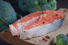 Raw salmon steak with sea salt, pepper and broccoli. On dark wooden surface Stock Photos