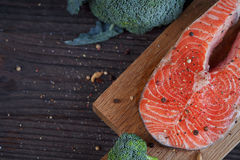 Raw salmon steak with sea salt, pepper and broccoli. On dark wooden surface Stock Photo