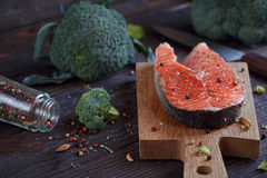 Raw salmon steak with sea salt, pepper and broccoli. On dark wooden surface Royalty Free Stock Images