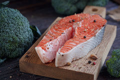 Raw salmon steak with sea salt, pepper and broccoli. On dark wooden surface Stock Images