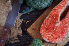 Raw salmon steak with sea salt, pepper and broccoli. On dark wooden surface Royalty Free Stock Image