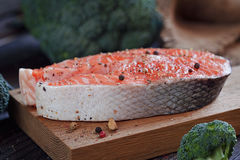 Raw salmon steak with sea salt, pepper and broccoli. On dark wooden surface Royalty Free Stock Photo
