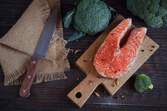 Raw salmon steak with sea salt, pepper and broccoli Royalty Free Stock Photo