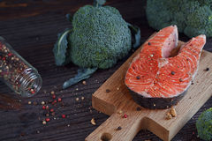 Raw salmon steak with sea salt, pepper and broccoli Stock Images