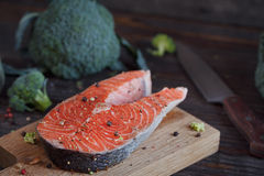Raw salmon steak with sea salt, pepper and broccoli Royalty Free Stock Image