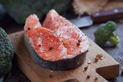 Raw salmon steak with sea salt, pepper and broccoli Stock Photo