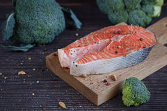 Raw salmon steak with sea salt, pepper and broccoli Royalty Free Stock Photography