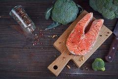 Raw salmon steak with sea salt, pepper and broccoli Royalty Free Stock Photos
