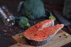 Raw salmon steak with sea salt, pepper and broccoli Stock Image