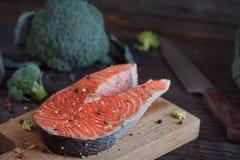 Raw salmon steak with sea salt, pepper and broccoli Stock Photos