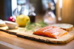 Raw salmon steak served with a lemon, dill and a whole wheat bread on a wooden cutting board. Close up of a fresh salmon steak fillet lying on a wooden plate Stock Photo