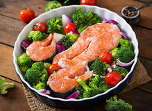 Raw salmon steak and vegetables. For cooking on a dark wooden background in a rustic style Stock Image