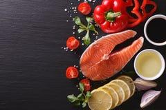 Raw salmon steak and vegetables on a slate board. Horizontal top. Raw salmon steak and vegetables on a slate board closeup. Horizontal top view Stock Photos