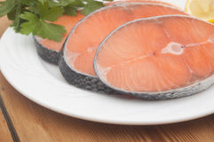 Raw salmon steak on white dish. Dish for baking with slices of salmon over wooden table Royalty Free Stock Images