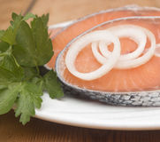 Raw salmon steak on white dish. Dish for baking with slices of salmon over wooden table Stock Photography