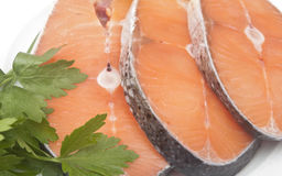 Raw salmon steak on white dish. Dish for baking with slices of salmon over wooden table Royalty Free Stock Photo