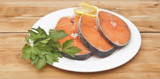 Raw salmon steak on white dish. Dish for baking with slices of salmon over wooden table Royalty Free Stock Image