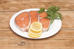 Raw salmon steak on white dish. Dish for baking with slices of salmon over wooden table Royalty Free Stock Photos