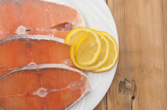 Raw salmon steak on white dish. Dish for baking with slices of salmon over wooden table Stock Photos