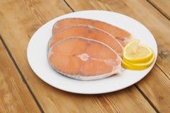 Raw salmon steak on white dish Royalty Free Stock Photos