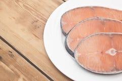 Raw salmon steak on white dish Royalty Free Stock Images