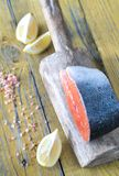 Raw salmon steak on the wooden board. Close up Stock Image