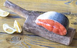 Raw salmon steak on the wooden board. Close up Royalty Free Stock Image