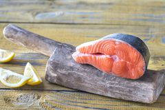 Raw salmon steak on the wooden board. Close up Stock Photos