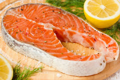 Raw salmon steak on wooden board. With salt, pepper, dill and lemon close up Stock Photos