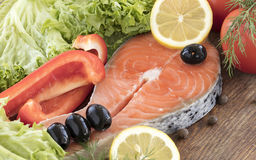 Raw salmon steak on a wooden board surrounded by vegetables, black olives and spices. Stock Photography